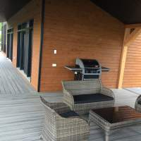 Sitting area and BBQ on covered deck at the Ilaali Chalet of Charlevoix.